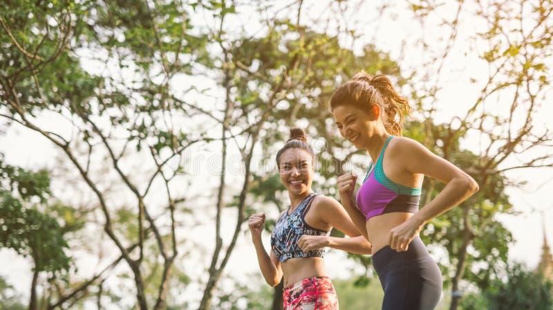 Atletische vrouw twee die in openlucht lopen Actie en gezond levensstijlconcept Aanstoten in werking gesteld in park royalty-vrije stock afbeelding