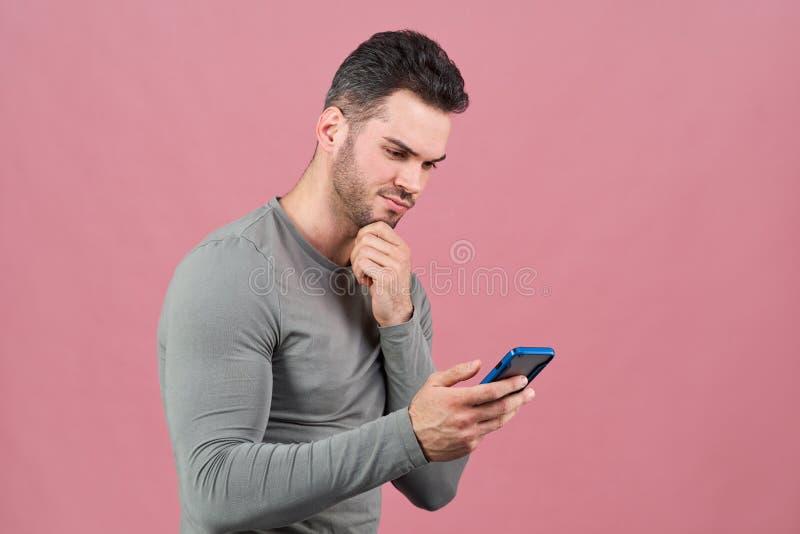 Atletische zekere smartphone van de jonge mensenholding ter beschikking en bekijkt zorgvuldig hem royalty-vrije stock foto