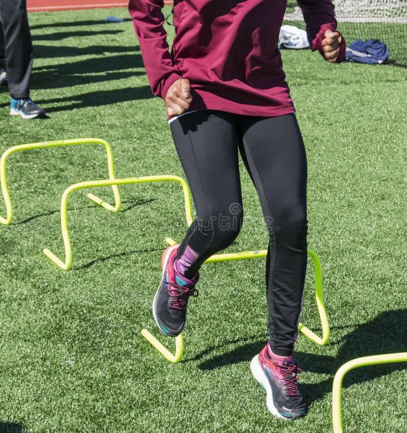 Atlety biega nad żółtymi mini przeszkodami fotografia royalty free
