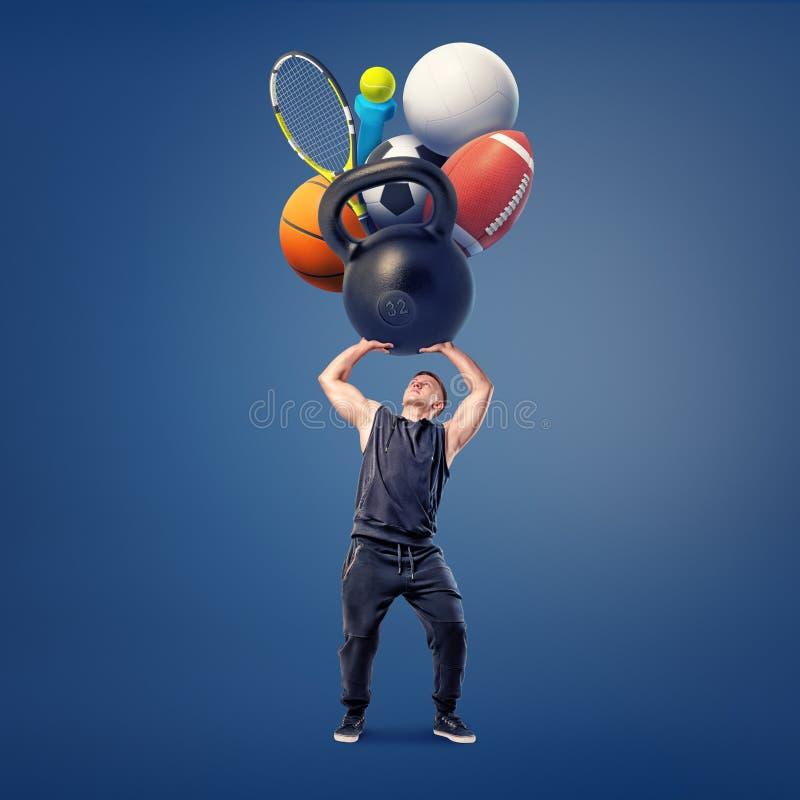 Atlety chwyty nad jego przewodzą gigantycznego ciężkiego kettlebell, dumbbell, racquet i kilka piłki dla różnych gier, zdjęcie stock