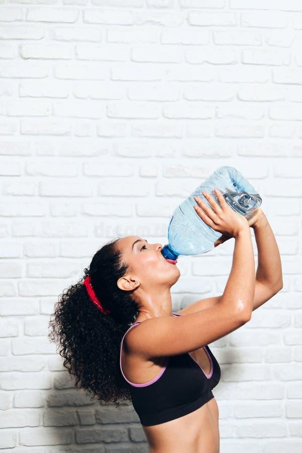 Atlety młodej kobiety woda pitna Od butelki Dla sport sprawności fizycznej zdjęcia stock