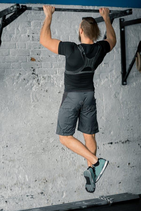 Atlety sprawności fizycznej samiec mięśniowy model ciągnie up na horyzontalnym barze w gym zdjęcia stock
