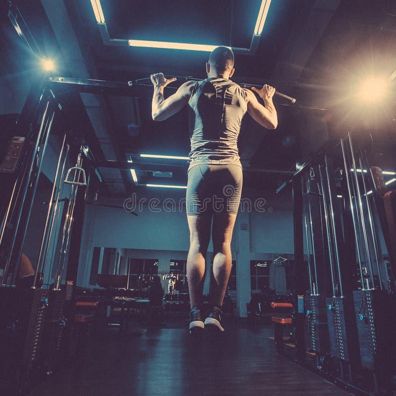 Atlety sprawności fizycznej samiec mięśniowy model ciągnie up w gym obraz tonujący zdjęcia stock
