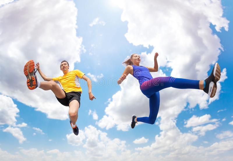 Atlety zostają w powietrzu podczas gdy skaczący przeciw niebu fotografia royalty free