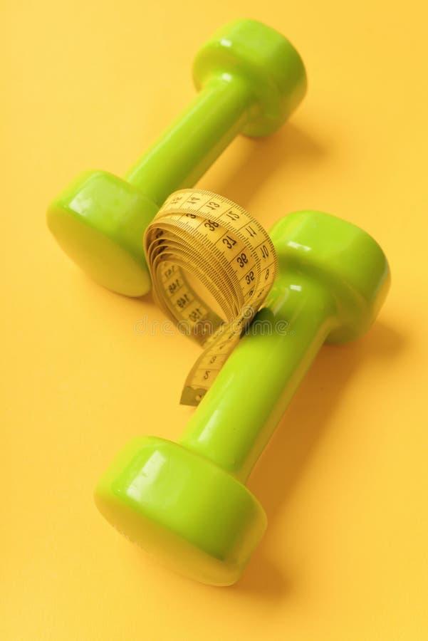 Atletyka i ciężar straty pojęcie Dumbbells w jaskrawym - zielony kolor zdjęcia stock