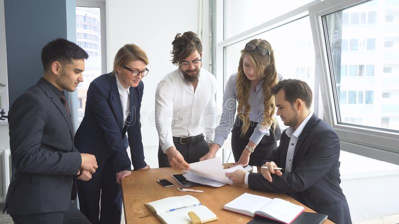 Atmósfera de funcionamiento en la oficina empleados para ver documentos en el lugar de trabajo Grupo de hombres de negocios de la foto de archivo