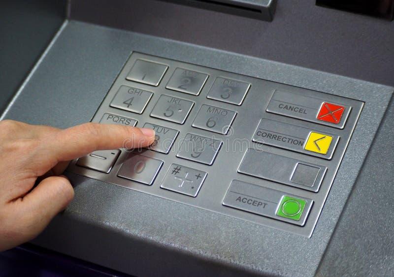 ATM-het close-up van de speldknoop en menselijke handwijsvinger royalty-vrije stock afbeelding