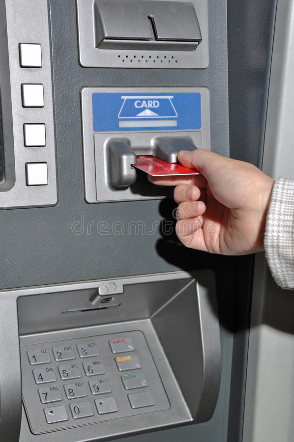 ATM machine. Woman inserting a card into a ATM machine stock images