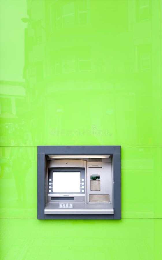 ATM-machine in groene muur die in zon glanzen. stock foto