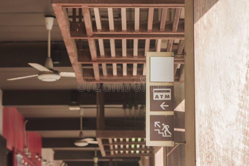 ATM och undertecknar uppför trappan på träetiketten som hänga på den konkreta högen med solljus utstråla från rättöverkanthörn royaltyfri bild
