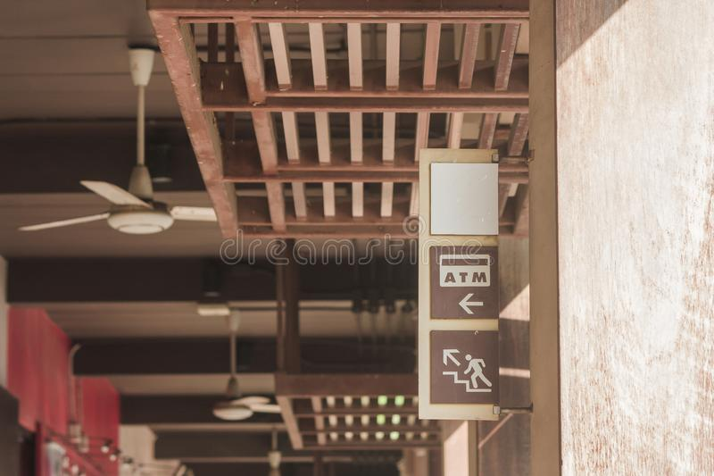 ATM and Upstairs Signs on wooden label that hanging on concrete pile with sunlight radiate from right top corner. royalty free stock image