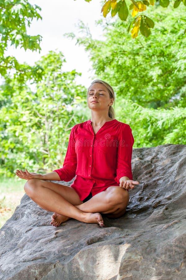 Atmendes blondes Mädchen, das unter einem Baum auf einem Stein meditiert lizenzfreie stockfotos