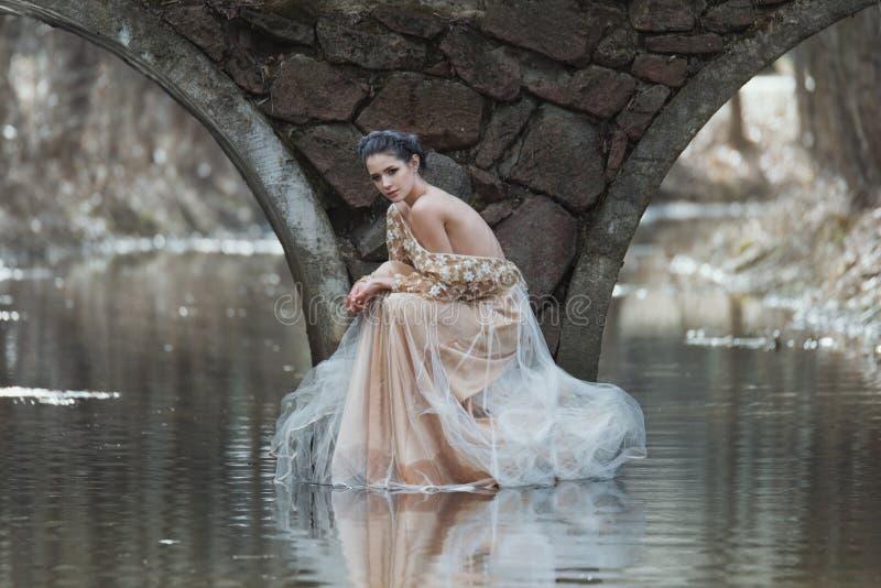 Atmosfärisk utomhus- stående av den sinnliga unga kvinnan som bär sammanträde för elegant klänning under bron av floden arkivfoto