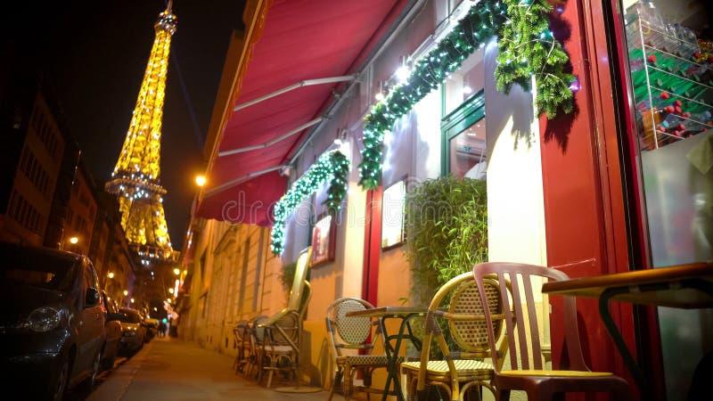 Atmosfera accogliente di Natale nella notte Parigi, vista dal caffè della via alla torre Eiffel fotografia stock libera da diritti