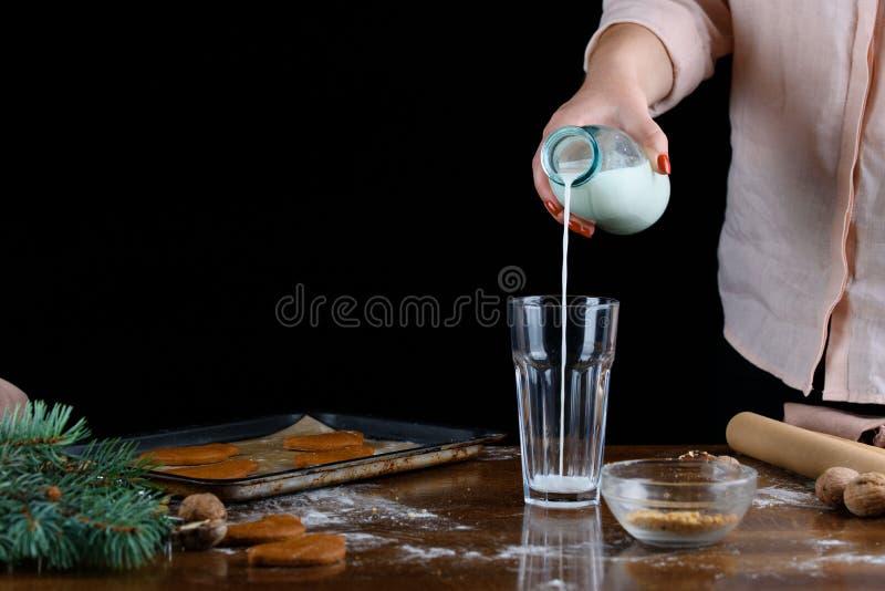 A atmosfera de feriados do Natal, o aroma do pão-de-espécie, ramos do abeto vermelho, presentes A mulher derrama o leite em um vi foto de stock royalty free