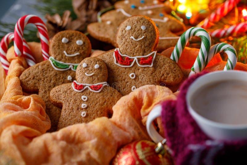 Atmosfera do Natal da mágica Pão-de-espécie e cacau quente em um copo com um lenço alegre Homens e bastões de doces pequenos de s fotografia de stock royalty free