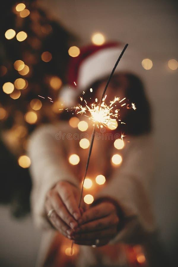 Atmosfera do partido da véspera de ano novo feliz Chuveirinho que queima-se à disposição da menina à moda no chapéu de Santa no f fotos de stock