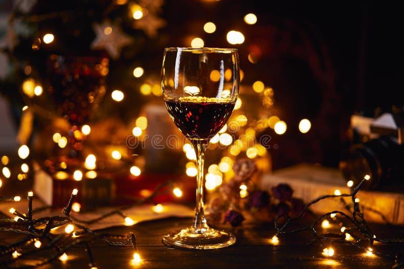 Atmosfera festiva nella sera con un vetro di vino rosso Bokeh leggero su fondo Natale, nuovo anno o san immagini stock