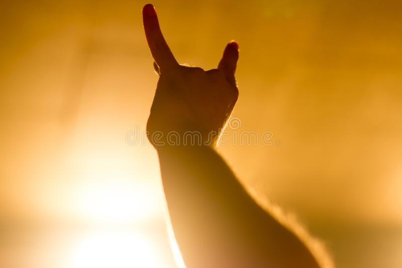 Atmosfera magica al concerto - gesto simbolico, mano sollevata sul concerto di musica nel riflettore giallo immagine stock libera da diritti