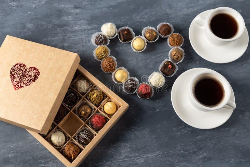 Atmosfera romântica dois xícaras de café, doces de chocolate e velas Dia feliz dos Valentim Copie o espaço fotografia de stock royalty free