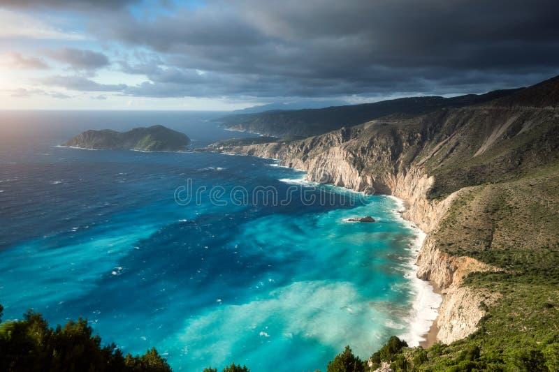 Atmosfera vaga sulla linea costiera dentellata pittoresca di Kefalonia Tempo offuscato, nuvole profonde, mare tempestoso e luce s immagini stock libere da diritti