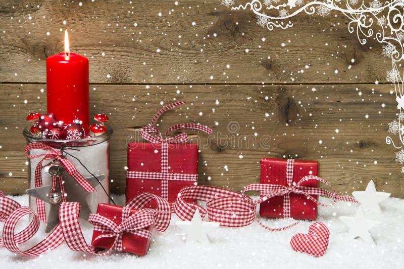 Atmosphärische Weihnachtskarte mit roter brennender Kerze und Geschenken stockbilder