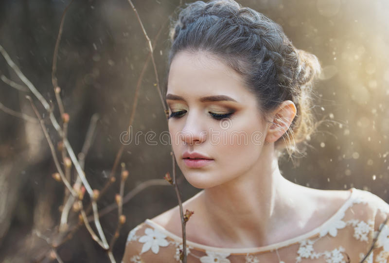 Atmosphärisches Porträt im Freien der sinnlichen jungen Frau, die elegantes Kleid in einem Koniferenwald mit Strahlen des Sonnenl lizenzfreies stockfoto