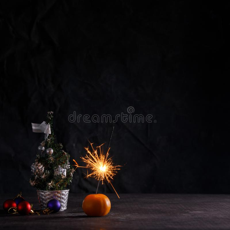 Atmosphere of the New Year. Card with Christmas decorations, a mandarin and a sparkler, with space for your text. New year party royalty free stock photo