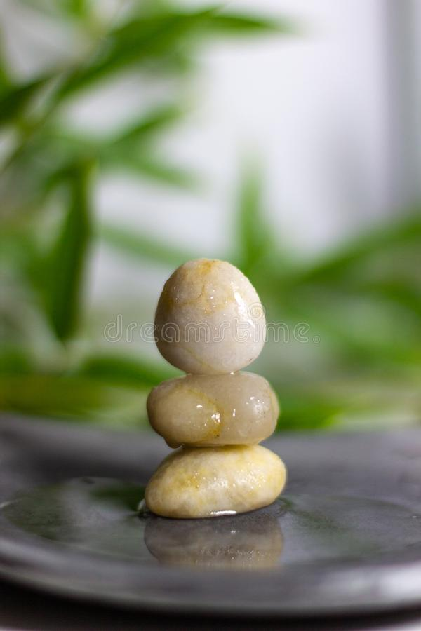 An atmosphere for a Zen moment. Bamboo leaves, stones in balance and water for a moment of zen stock photos