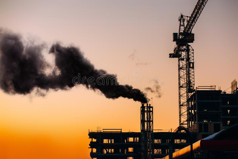 Atmospheric air pollution from industrial smoke. Crane and build royalty free stock photography