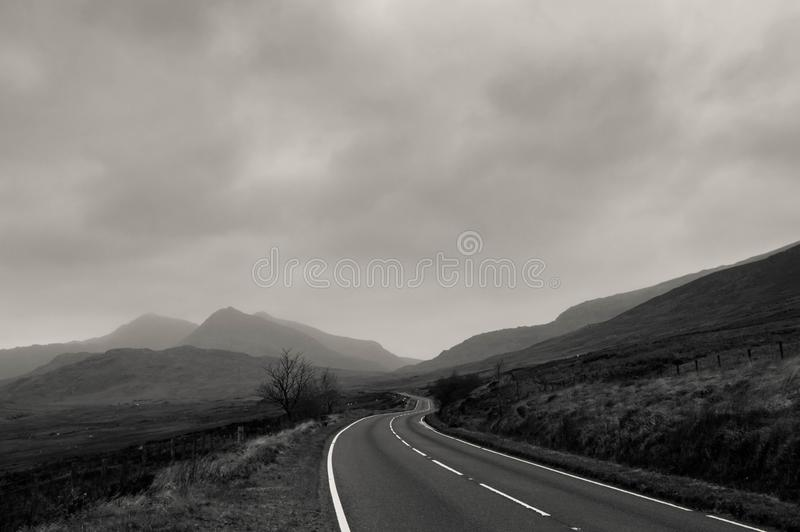 An atmospheric black and white edit of a road heading towards mountains on a stormy winters day. Snowdonia, Wales. UK. royalty free stock image