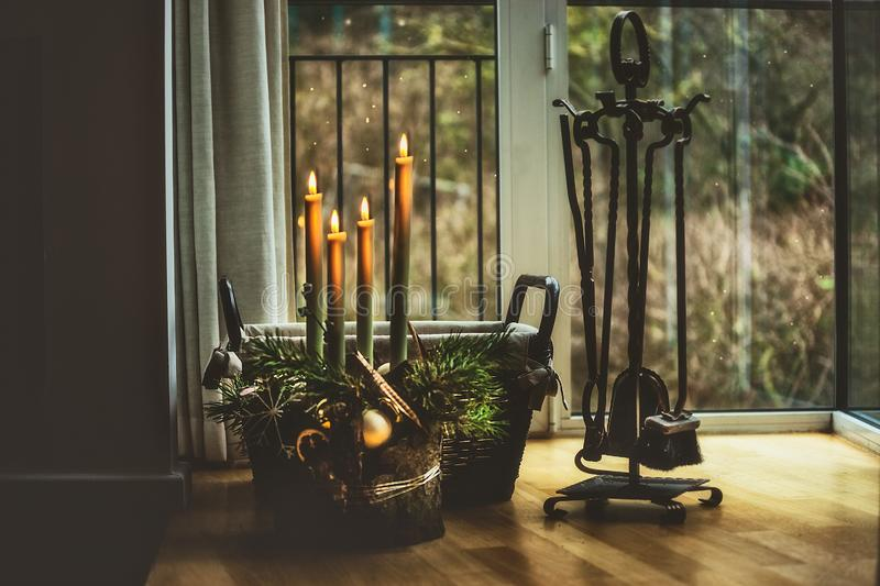 Atmospheric Christmas time at home. Advent wreath with burning candles at window in dark room with fire irons stock photos