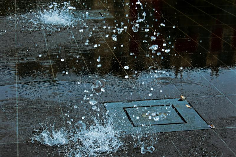 Atmospheric falling fountain water drops splashes on smooth shiny dark ceramic tiles with reflections royalty free stock photos