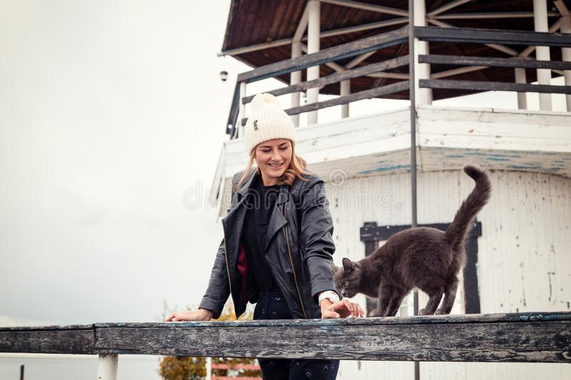 Atmospheric lifestyle photo. Of young beautiful darkhaired woman in knitting hat, in a leather jacket and black trousers walks and plays with a cat against the stock images
