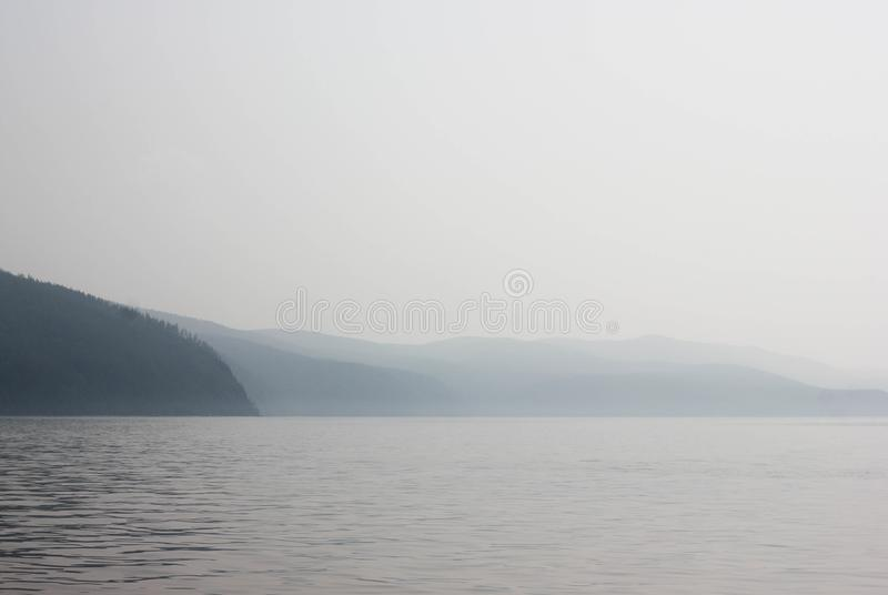 Atmospheric marine landscape with mountain. Atmospheric marine landscape with calm water and dark mountains in a fog. Chill foggy picture, concept of tranquility stock photo