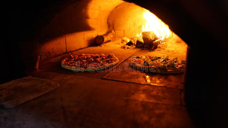 Two pizzas in stone oven is cooking. stock image