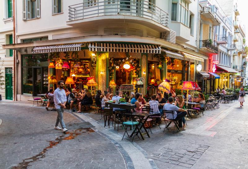 Atmospheric scene of people sitting at an Athens cafeteria late royalty free stock photography