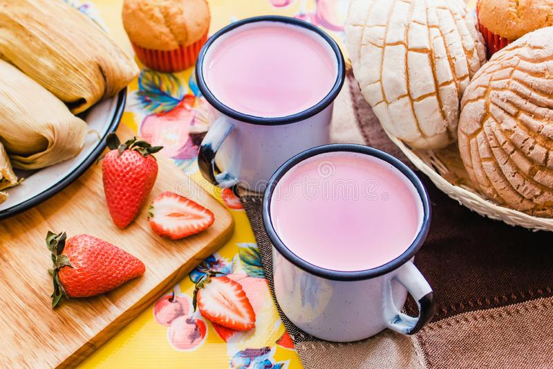Atole de fresa, mexican traditional beverage and bread, Made with cinnamon and strawberries in Mexico. Mexican breakfast royalty free stock image