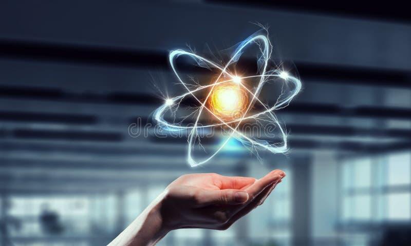 Atom icon in palm . Mixed media . Mixed media stock photo