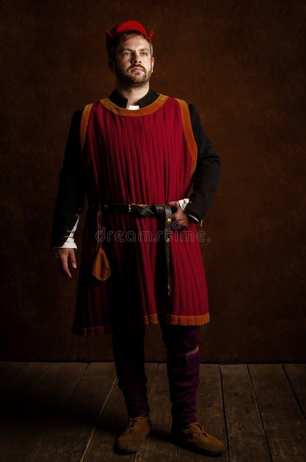 Ator do homem em um traje do século XV medieval em um fundo estilizado envelhecido Passatempo, reconstrução da vida medieval foto de stock