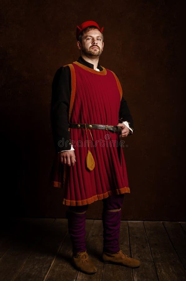 Ator do homem em um traje do século XV medieval em um fundo estilizado envelhecido Passatempo, reconstrução da vida medieval fotografia de stock