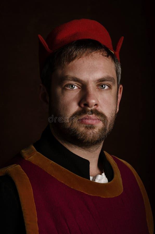 Ator do homem em um traje do século XV medieval em um fundo estilizado envelhecido Passatempo, reconstrução da vida medieval fotografia de stock royalty free