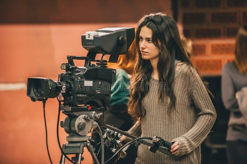 Atrás da cena A cena fêmea do filme do tiro do operador cinematográfico com veio foto de stock