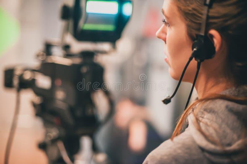 Atrás da cena A cena fêmea do filme do tiro do operador cinematográfico com veio imagem de stock