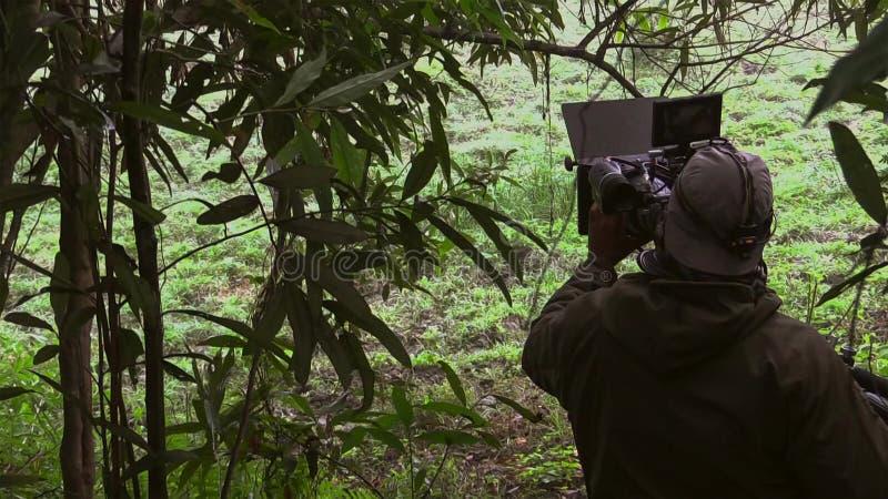 Atrás da cena O tiro do operador cinematográfico e do realizador de cinema filma a cena no lugar exterior fotos de stock