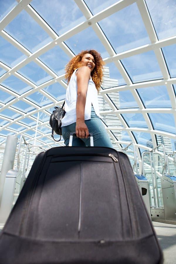 Atrás da jovem mulher feliz do curso que anda com a mala de viagem na estação fotografia de stock royalty free