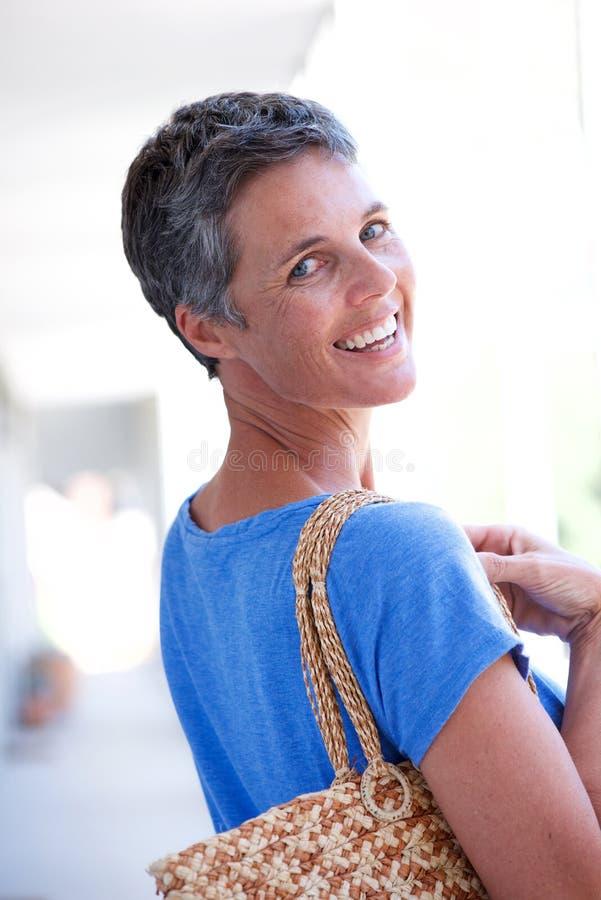Atrás da mulher feliz com o saco que gira ao redor fotografia de stock royalty free
