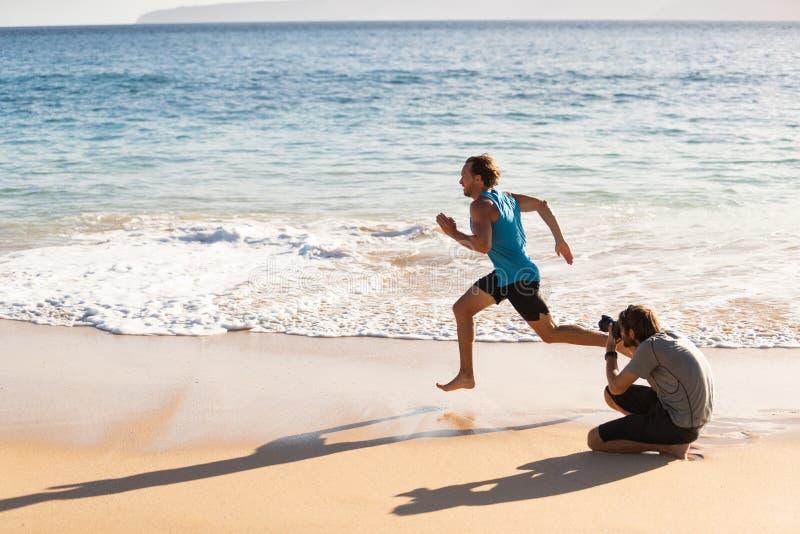 Atrás das cenas da sessão fotográfica do modelo masculino do atleta dos esportes que corre para o fotógrafo que toma imagens para foto de stock