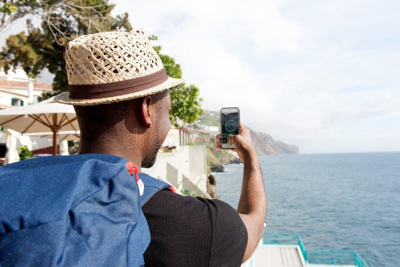 Atrás do homem afro-americano do curso com o saco que olha de tomada o selfie pelo mar fotografia de stock