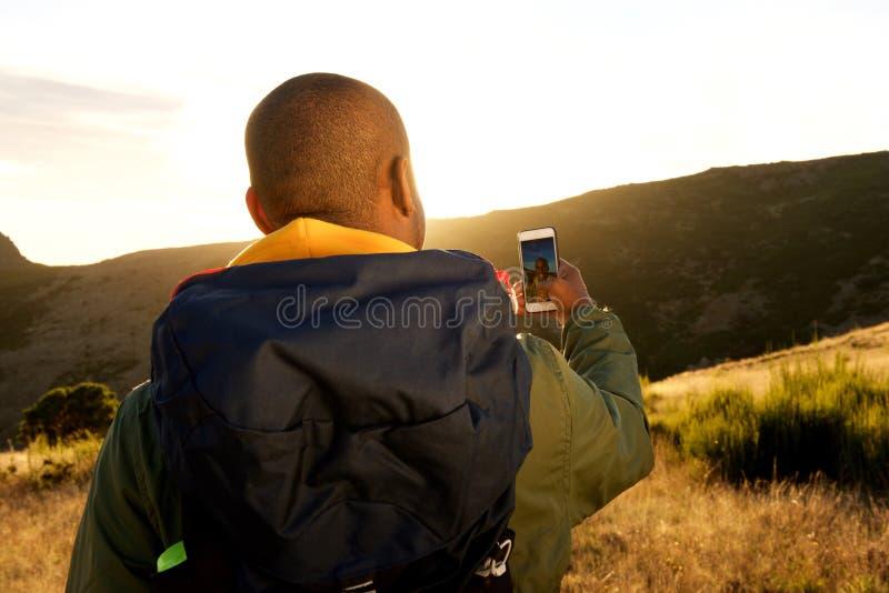 Atrás do homem afro-americano que caminha com o telefone celular que toma o selfie nas montanhas fotografia de stock
